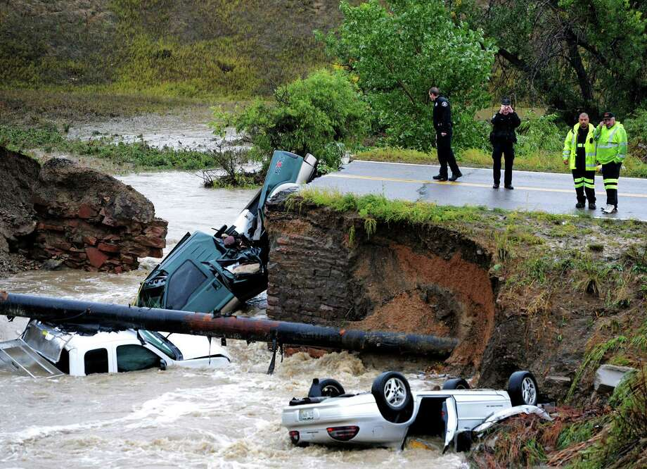 """Officials investigate the scene of a road collapse at Highway 287 and Dillon at the Broomfield/Lafayette border, Colo., that sent three vehicles into the water after flash flooding on Thursday, Sept. 12, 2013. The National Weather Service has warned of an """"extremely dangerous and life-threatening situation"""" throughout the region. (AP Photo/Daily Camera, Cliff Grassmick)  ORG XMIT: COBOU111 Photo: Cliff Grassmick / Daily Camera"""