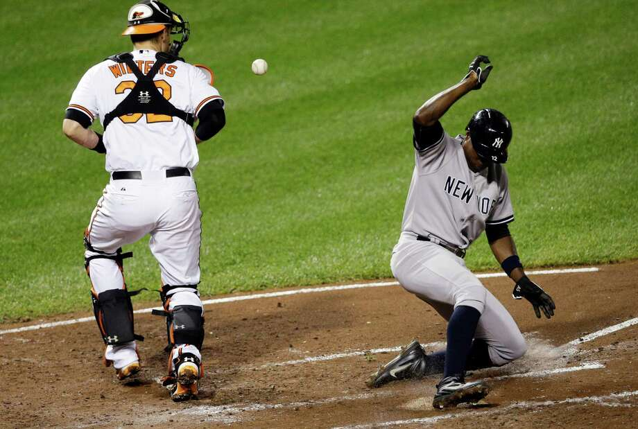 New York Yankees' Alfonso Soriano, right, slides into home plate for a run on a single by Vernon Wells as Baltimore Orioles catcher Matt Wieters tries to get hold of the ball in the third inning of a baseball game, Thursday, Sept. 12, 2013, in Baltimore. (AP Photo/Patrick Semansky) ORG XMIT: MDPS107 Photo: Patrick Semansky / AP