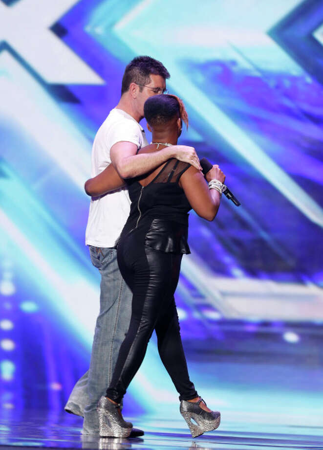 THE X FACTOR: Simon Cowell escorts contestant Jocelyn Hinton from the stage on THE X FACTOR airing Thursday, Sep. 12 (8:00-10:00 PM ET/PT) on FOX. CR: Ray Mickshaw/ FOX. © Copyright 2013 / FOX.