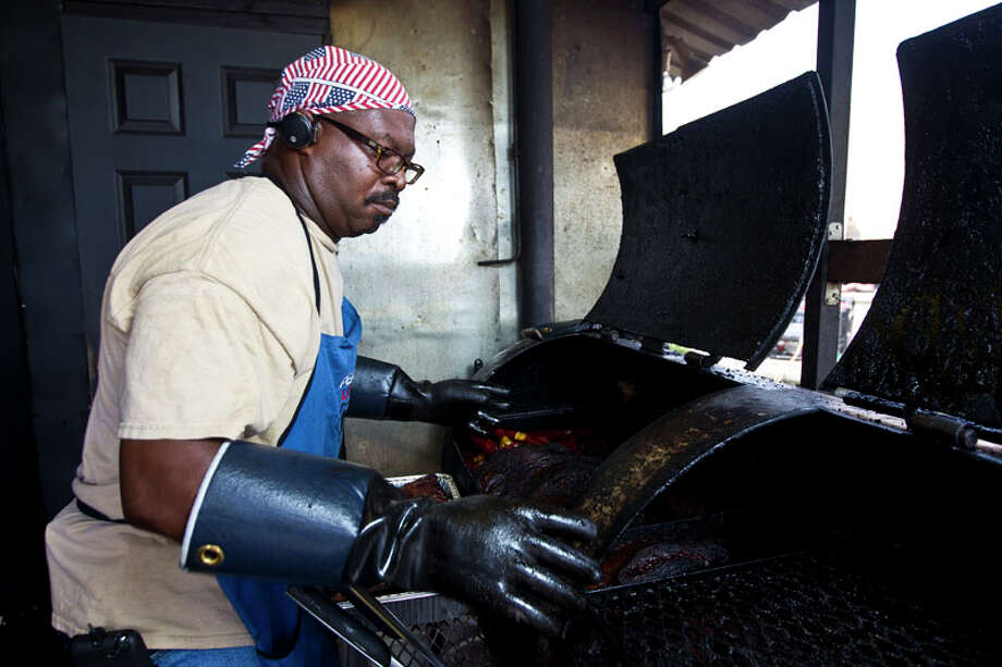 Trent Brooks, owner of Brooks Place BBQ pulls meat from his smoker before he opens his barbecue joint for business, Friday, June 21, 2013, in Cypress. ( Nick de la Torre / Houston Chronicle ) Photo: Nick De La Torre, Houston Chronicle / © 2013  Houston Chronicle