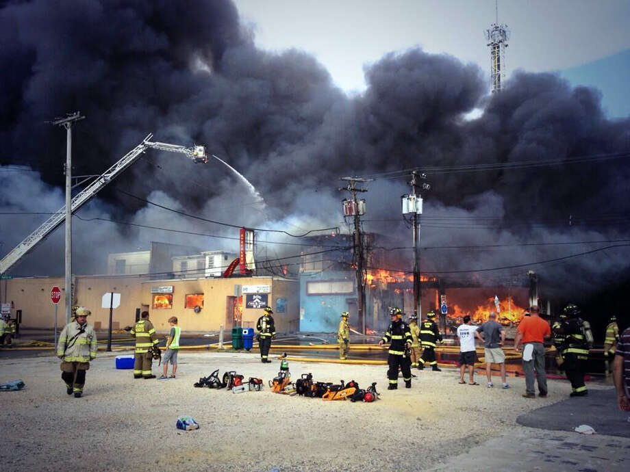 Firefighters battle a raging fire on the boardwalk in Seaside Heights, N.J. that apparently started in an ice cream shop and has spread several blocks down, Thursday, Sept. 12, 2013. The boardwalk was damaged in Superstorm Sandy and was being repaired. (AP Photo/The Asbury Park Press, Kristi Funderburk)  MANDATORY CREDIT: PAPER AND PHOTOGRAPHER; NO SALES ORG XMIT: NJASB101 Photo: Kristi Funderburk, AP / The Asbury Park Press