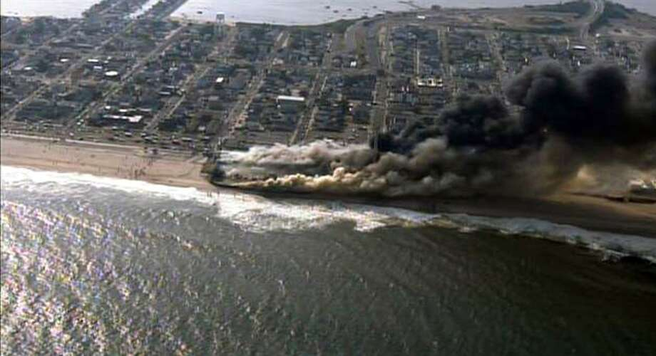 This frame grab from video provided by Fox 29 shows a raging fire in Seaside Park, N.J. on Thursday, Sept. 12, 2013.  The fire apparently started in an ice cream shop and spread several blocks down  the New Jersey shore boardwalk that was damaged in Superstorm Sandy (AP Photo/Fox 29) MANDATORY CREDIT ORG XMIT: NYKS101 Photo: AP / Fox 29
