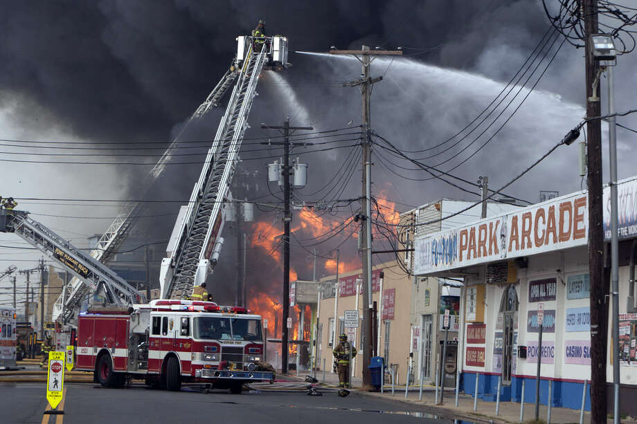 Firefighters battle a fire on the Seaside Heights, N.J. boardwalk Thursday, Sept. 12, 2013. The fire started in the vicinity of an ice cream shop and burned several blocks of boardwalk and businesses in a town that was still rebuilding from damage caused by Superstorm Sandy. (AP Photo/The Asbury Park Press, Bob Bielk)  NO SALES ORG XMIT: NJASB110 Photo: Bob Bielk, AP / The Asbury Park Press