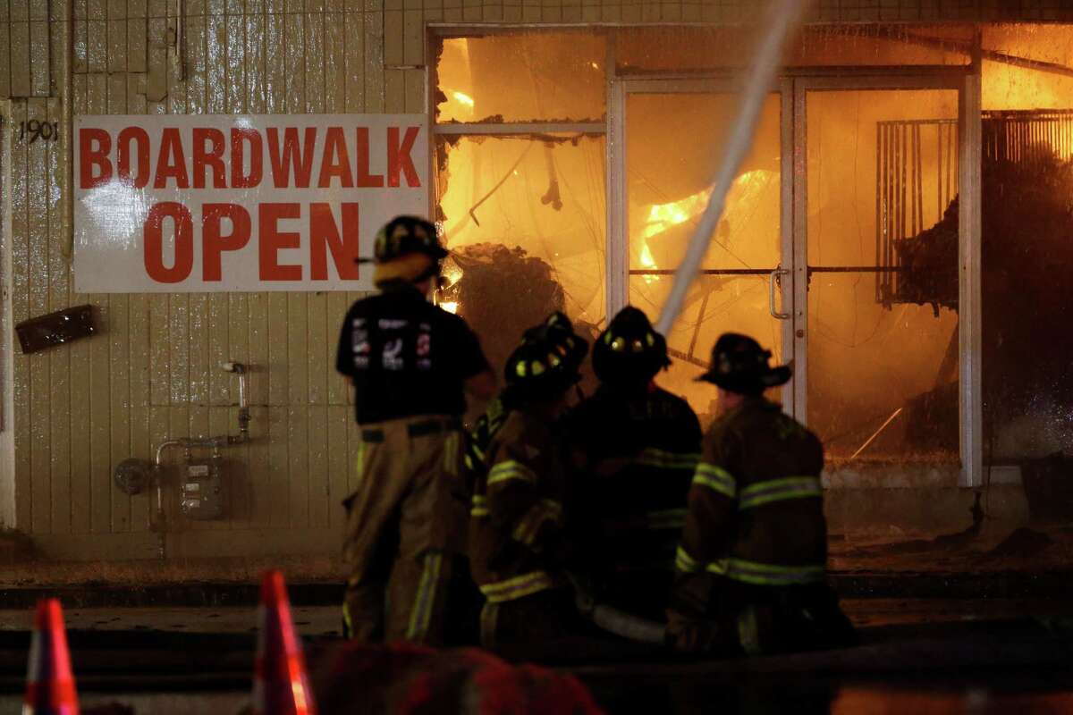 Firefighters battle a blaze in a building on the Seaside Park boardwalk on Thursday, Sept. 12, 2013, in Seaside Park, N.J. The fire began in a frozen custard stand on the Seaside Park section of the boardwalk and quickly spread north into neighboring Seaside Heights. (AP Photo/Julio Cortez) ORG XMIT: NJJC114