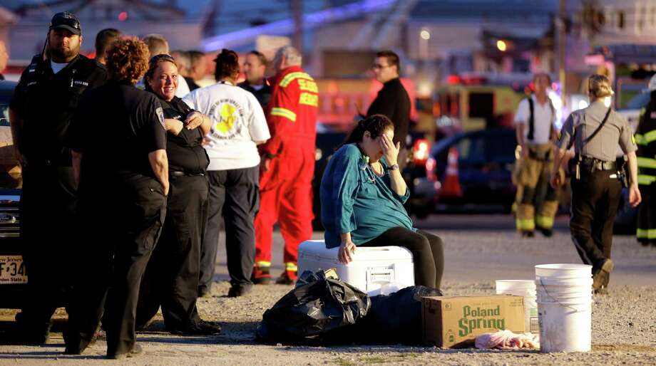 A woman puts her hand over her face as she sits on a cooler in an area for first responders working a massive fire at the Seaside Park boardwalk, Thursday, Sept. 12, 2013, in Seaside Park, N.J. The fire, which apparently started in an ice cream shop and spread several blocks, hit the recently repaired boardwalk, which was damaged last year by Superstorm Sandy. There were no other early reports of any injuries. (AP Photo/Julio Cortez) ORG XMIT: NJJC123 Photo: Julio Cortez, AP / AP