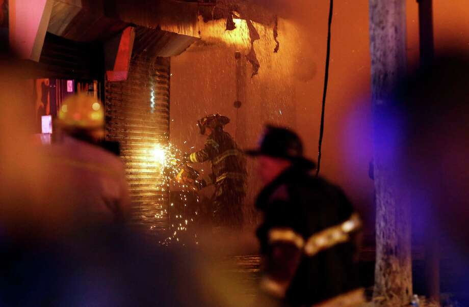 A firefighter saws through a metal wall on a building while battling a fire at the Seaside Park boardwalk on Thursday, Sept. 12, 2013, in Seaside Park, N.J. The fire began in a frozen custard stand on the Seaside Park section of the boardwalk and quickly spread north into neighboring Seaside Heights. (AP Photo/Julio Cortez) ORG XMIT: NJJC120 Photo: Julio Cortez, AP / AP