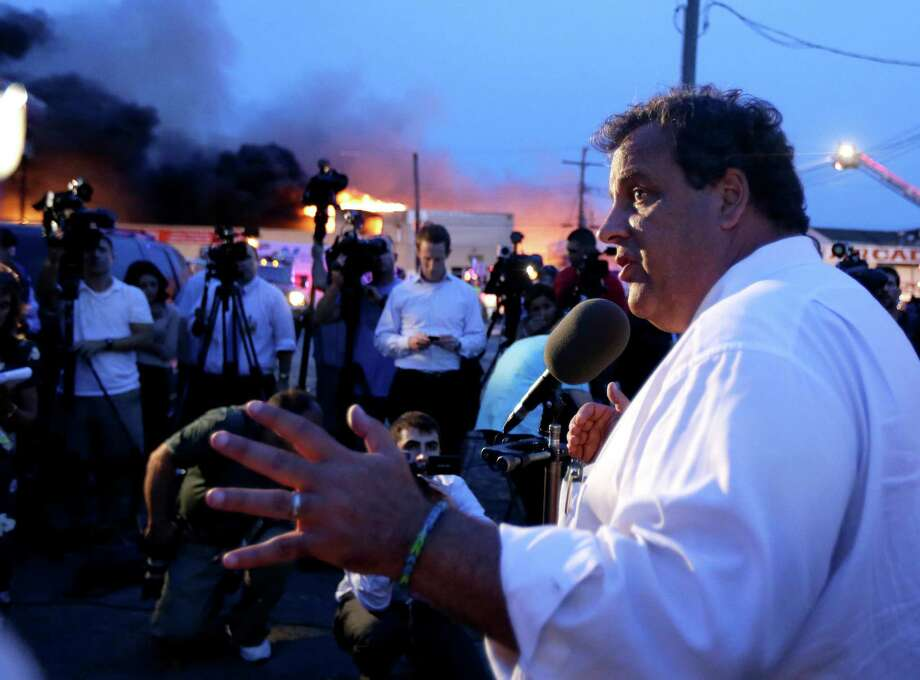 New Jersey Gov. Chris Christie addresses the media near the area hit by a massive fire on Thursday, Sept. 12, 2013, in Seaside Park, N.J. Firefighters battle a blaze in a building on the Seaside Park boardwalk on Thursday, Sept. 12, 2013, in Seaside Park, N.J. The fire began in a frozen custard stand on the Seaside Park section of the boardwalk and quickly spread north into neighboring Seaside Heights. (AP Photo/Julio Cortez) ORG XMIT: NJJC126 Photo: Julio Cortez, AP / AP