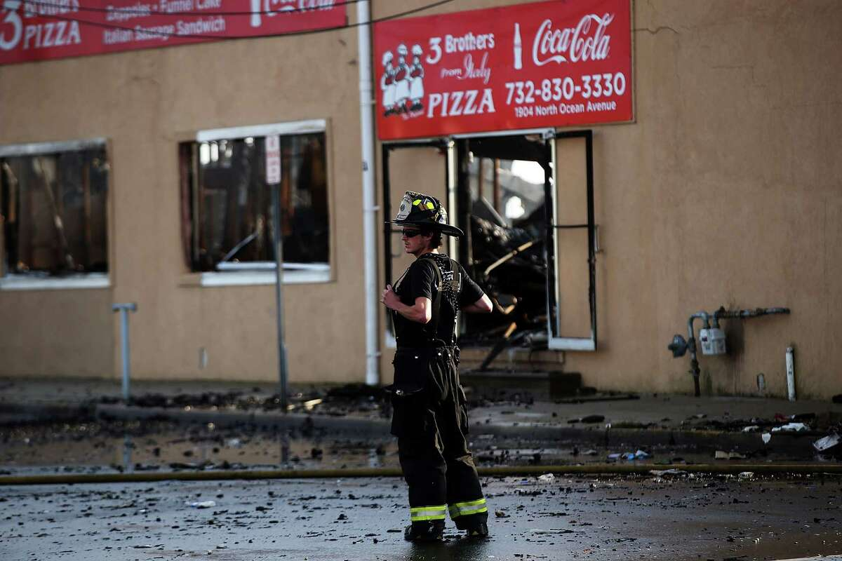 SEASIDE HEIGHTS, NJ - SEPTEMBER 13: A firefighter stands at the scene of a massive fire that destroyed dozens of businesses along an iconic Jersey shore boardwalk on September 13, 2013 in Seaside Heights, New Jersey. The 6-alarm fire began in a frozen custard stand on the recently rebuilt boardwalk around 2:00 p.m. on Thursday, September 12, and quickly spread in high winds. While there were no injuries reported, many businesses that had only recently re-opened after Hurricane Sandy were destroyed in the blaze. (Photo by Spencer Platt/Getty Images) ORG XMIT: 180621484