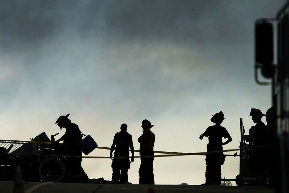 SEASIDE HEIGHTS, NJ - SEPTEMBER 13:  Firefighters stand at the scene of a massive fire that destroyed dozens of businesses along an iconic Jersey shore boardwalk on September 13, 2013 in Seaside Heights, New Jersey. The 6-alarm fire began in a frozen custard stand on the recently rebuilt boardwalk around 2:00 p.m. on Thursday, September 12, and quickly spread in high winds. While there were no injuries reported, many businesses that had only recently re-opened after Hurricane Sandy were destroyed in the blaze.  (Photo by Spencer Platt/Getty Images) ORG XMIT: 180621484 Photo: Spencer Platt, Getty / 2013 Getty Images