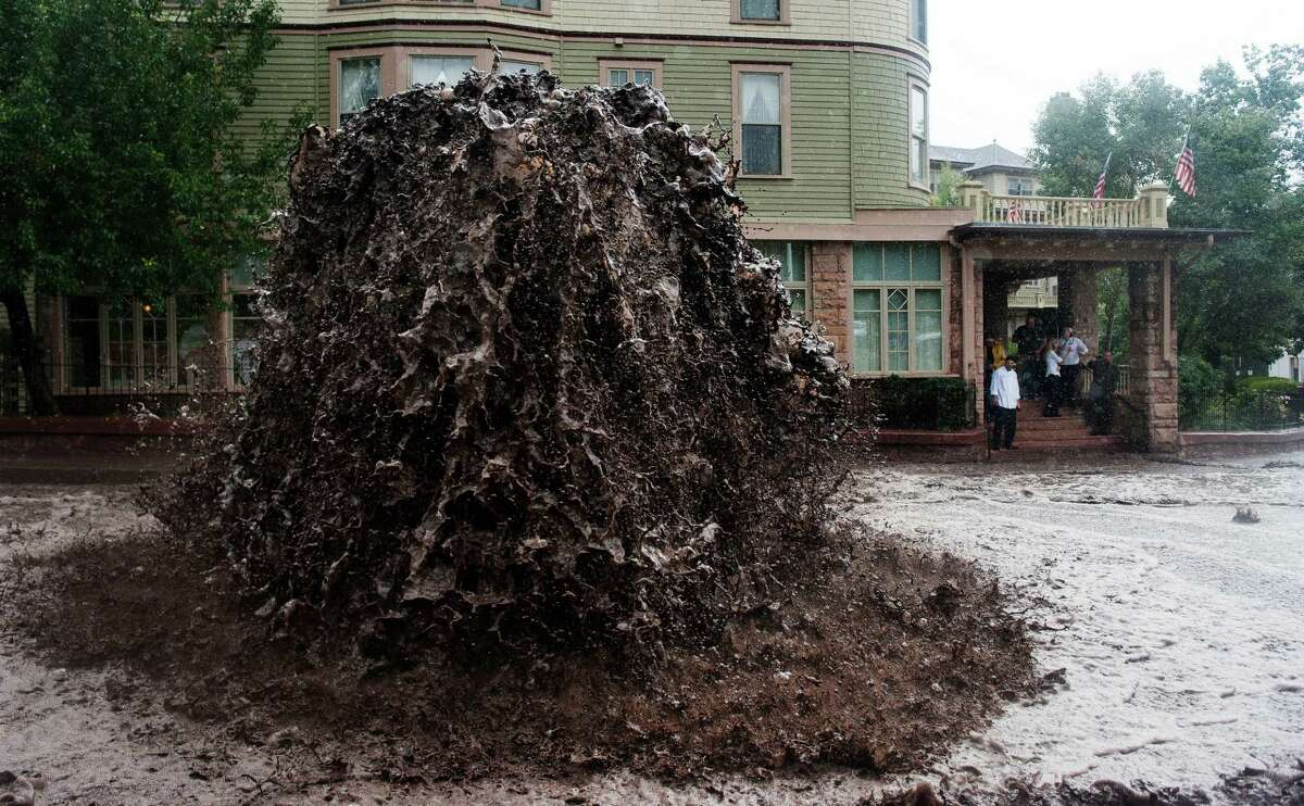 Flood water shoots out of a sewer on Canon Avenue next to the Cliff House in Manitou Springs, Colo. Thursday, Sept. 12, 2013 as storms continue to dump rain over the Waldo Canyon burn scar. (AP Photo/The Gazette, Michael Ciaglo) ORG XMIT: COCOL101