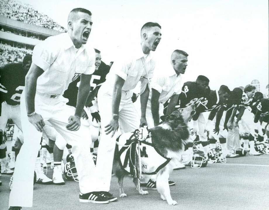 Senior Yell Leaders Rick Hamilton (1989), Steve Keathley (1989) and Ronnie Bolton (1989) with Reveille sing the Spirit of Aggieland at the 1988 Texas A&M football team.
