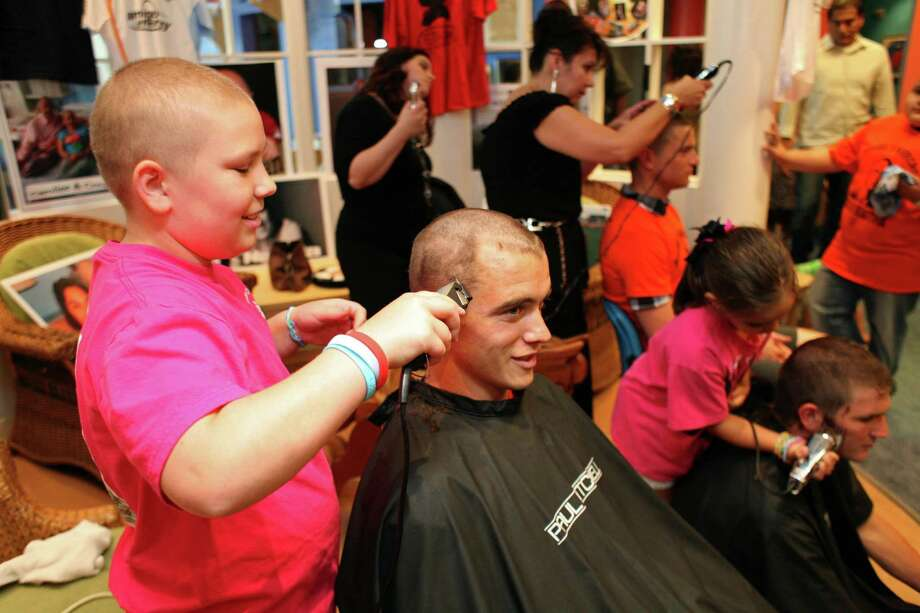 Caroline Fitzgerald (left), 11, of Houston, who is receiving treatment for Leukemia at Texas Children's Hospital, shaves the head of Cameron Weaver with the Houston Dynamo soccer team as he and his teammates had their heads shaved by cancer patients at the Texas Children's Cancer Center to benefit and raise awareness for the Dynamo's Craig Waibel's Warriors Bald is Beautiful fundraising event  Wednesday, May 26, 2010, in Houston.