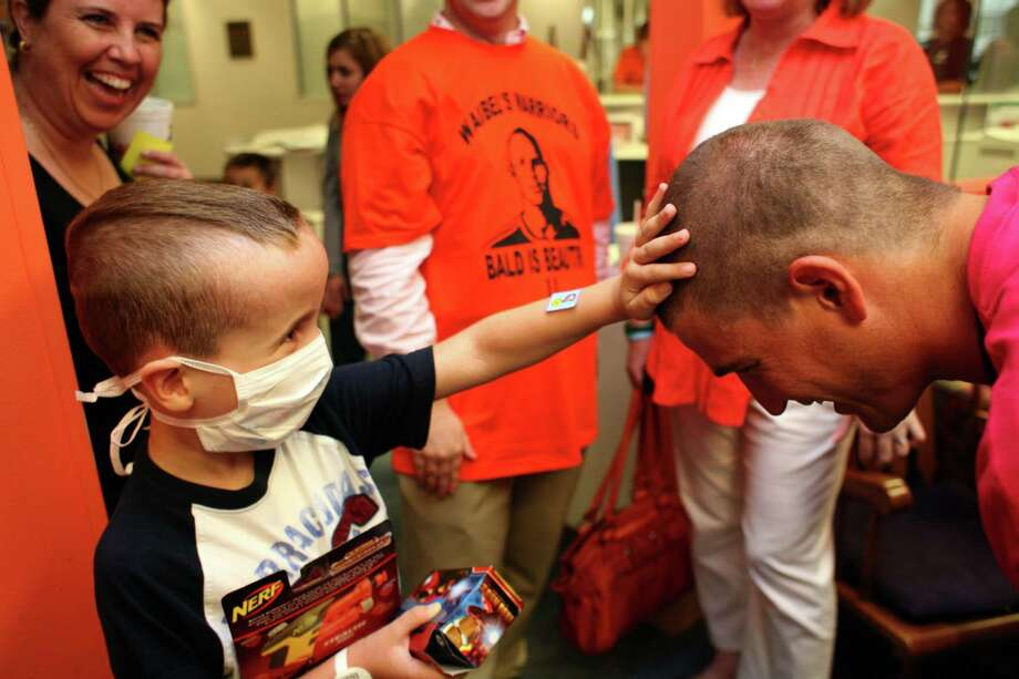 Peter Tsatsaronis, 7, who is receiving cancer treatments at Texas Children's Hospital, touches the freshly shaved head of Bobby Boswell, of the Houston Dynamo soccer team, as he and his teammates had their heads shaved by cancer patients at the Texas Children's Cancer Center to benefit and raise awareness for the Dynamo's Craig Waibel's Warriors Bald is Beautiful fundraising event  Wednesday, May 26, 2010, in Houston.