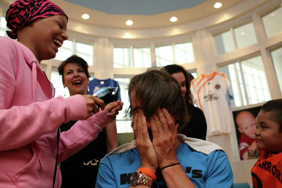 Devin Duncan (left), 17, of Houston, who is receiving cancer treatments at Texas Children's Hospital, laughs as she begins to shaves the head of Michael Chabala, of the Houston Dynamo soccer team, as he and his teammates had their heads shaved by cancer patients at the Texas Children's Cancer Center to benefit and raise awareness for the Dynamo's Craig Waibel's Warriors Bald is Beautiful fundraising event  Wednesday, May 26, 2010, in Houston.