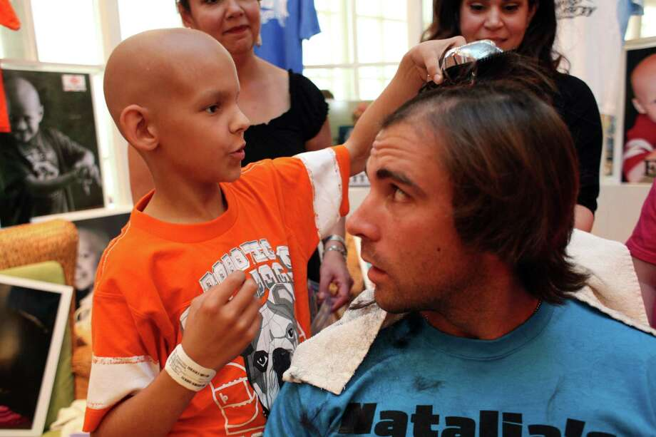Brennan Daigle, 9, of West Lake, La., who is receiving cancer treatments at Texas Children's Hospital, begins to shave the head of Michael Chabala, of the Houston Dynamo soccer team, as he and his teammates had their heads shaved by cancer patients at the Texas Children's Cancer Center to benefit and raise awareness for the Dynamo's Craig Waibel's Warriors Bald is Beautiful fundraising event  Wednesday, May 26, 2010, in Houston.