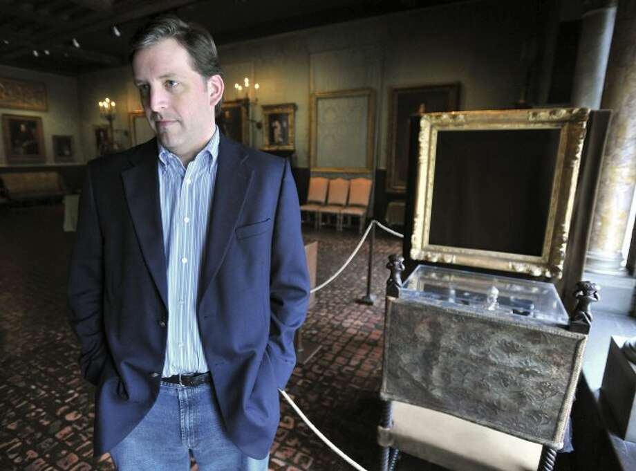 """Stealing Rembrandts"" Author Anthony Amore stands beside an empty frame at the Gardner Museum"
