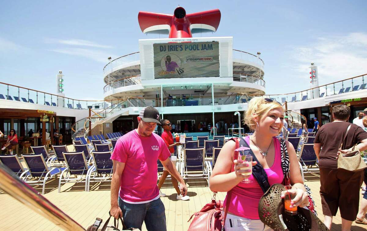 Shelby Gilson, front, and Roy Evans, both of Hico, Texas, walk across the pool deck to check into their room as they board the Carnival Triumph cruise ship, Thursday, June 13, 2013, at the Port of Galveston in Galveston.