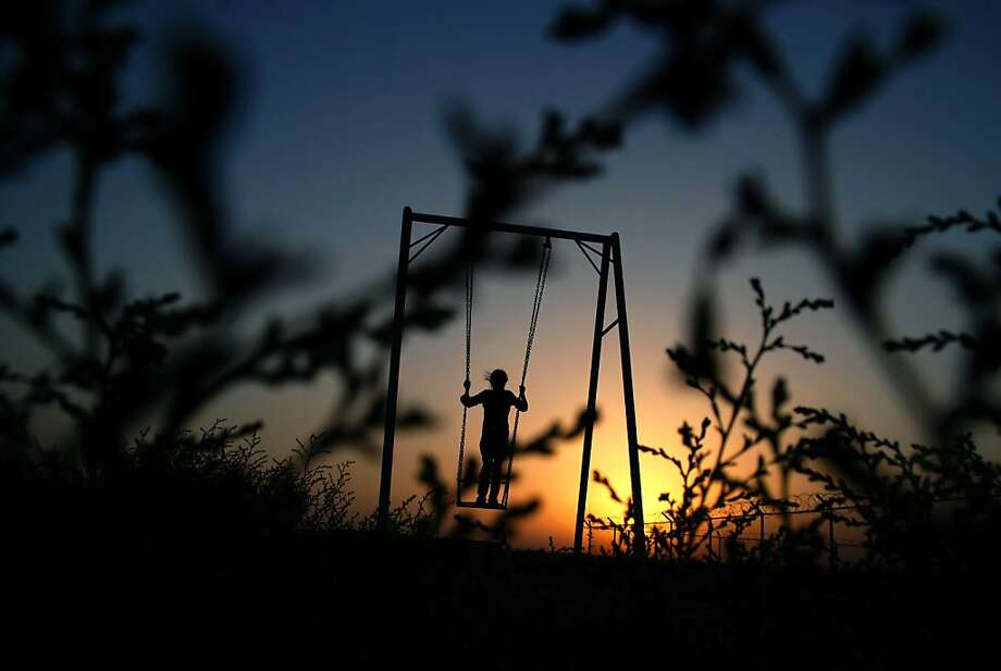 Riding into the sunset:A girl swings in a playground  on the outskirts of Mazar-e-Sharif, Afghanistan. Photo: Mustafa Najafizada, Associated Press