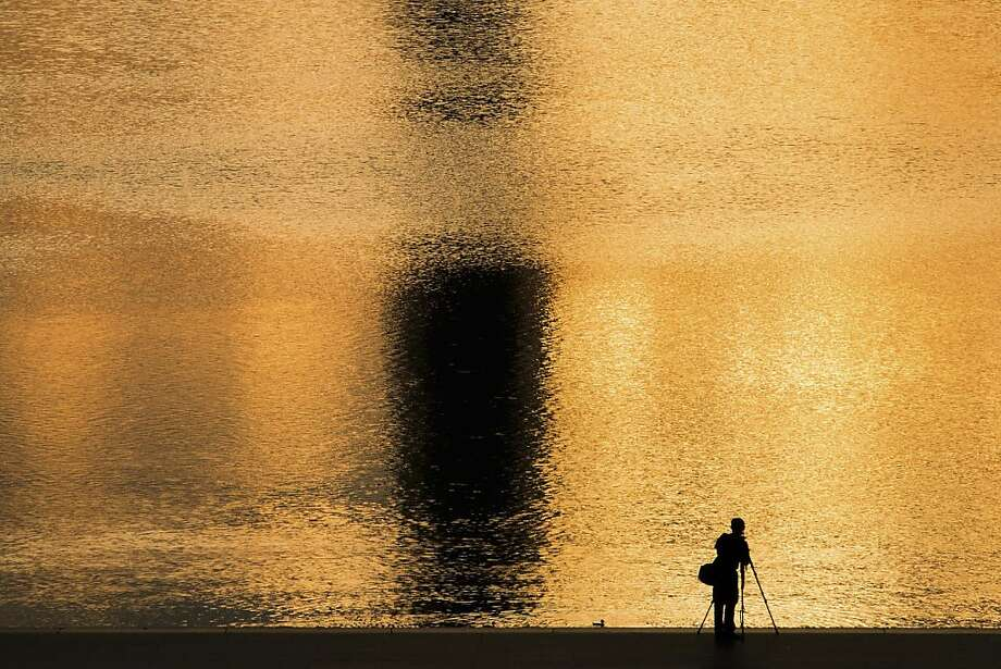 A photographer captures the moment in the reflecting pool at sunrise near the Lincoln Memorial in 