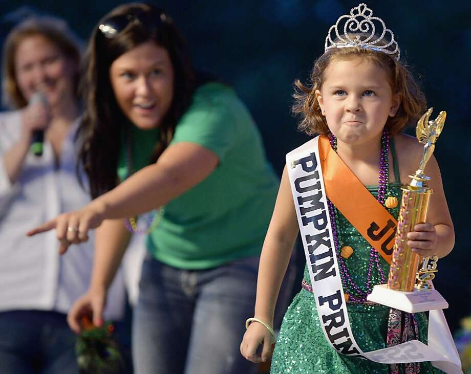 The imperious Pumpkin Princess:Having won the coveted title of Pumpkin Princess of the Morton Pumpkin Festival in Morton, Ill., 5-year-old Julia Polhans is determined to exercise her authority over her squash subjects. Photo: Ron Johnson, Associated Press