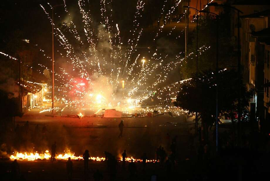 Ooh pretty:Protesters set off fireworks next to riot police during a demonstration in Ankara against the planned construction of a cultural center containing an Alevi cemevi (house of worship) and a Sunni mosque side by side. Photo: Adem Altan, AFP/Getty Images