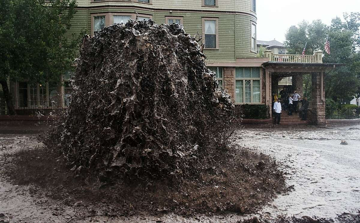 Hello, Roto-Rooter? Water gushes out of a sewer on Canon Avenue next to the Cliff House in Manitou Springs, Colo. Flooding caused by days of rain cut off mountain communities and forced evacuations along Colorado's Front Range.