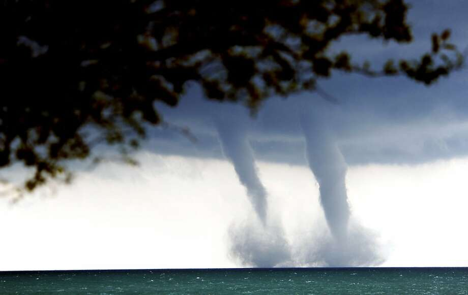 Race you to the shore! A pair of water spouts form on Lake Michigan southeast of Kenosha, Wis. A water spout is basically a relatively weak tornado over water. Photo: Kevin Poirier, Associated Press