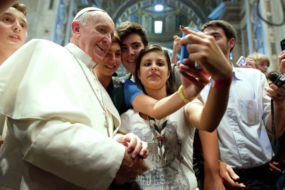 Pope Francis poses with youth in the Church of Saint Augustine in downtown Rome. Avoid the awkward