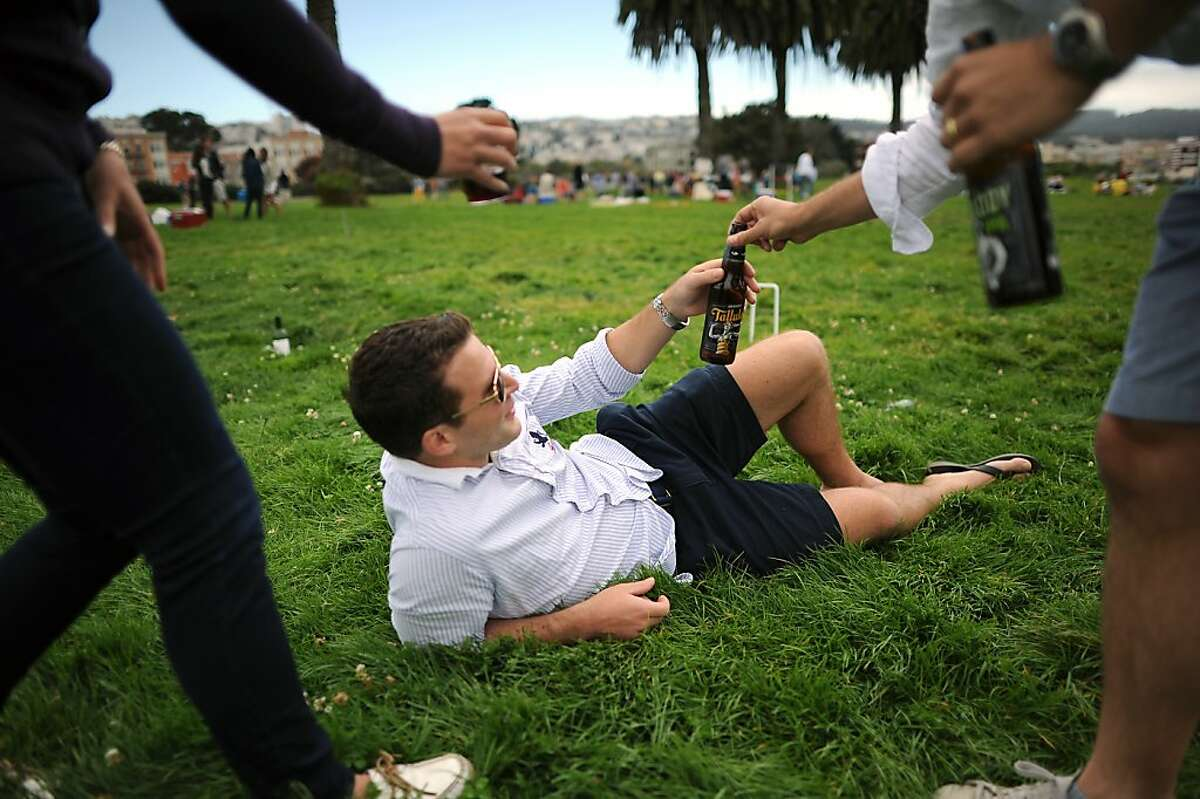 A friend hands Steven Reymond a beer as he relaxes in the grass during a break in his croquet game at the Fort Mason Great Meadow in San Francisco, California, Saturday August 17, 2013.
