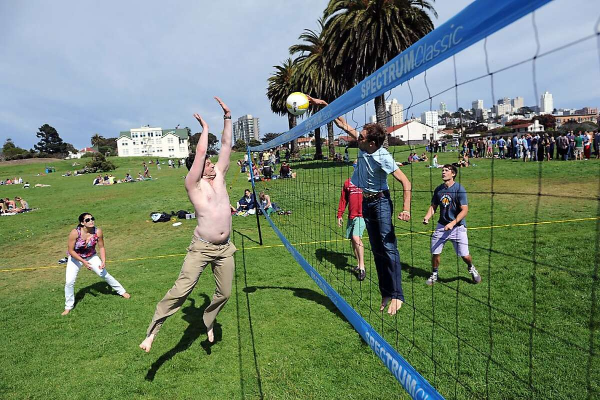 Jake Kopperman (left) tries to block a shot by Jeff Schneider during a game of volleyball at Fort Mason's Great Meadow, where mostly young men come to play sports and party.