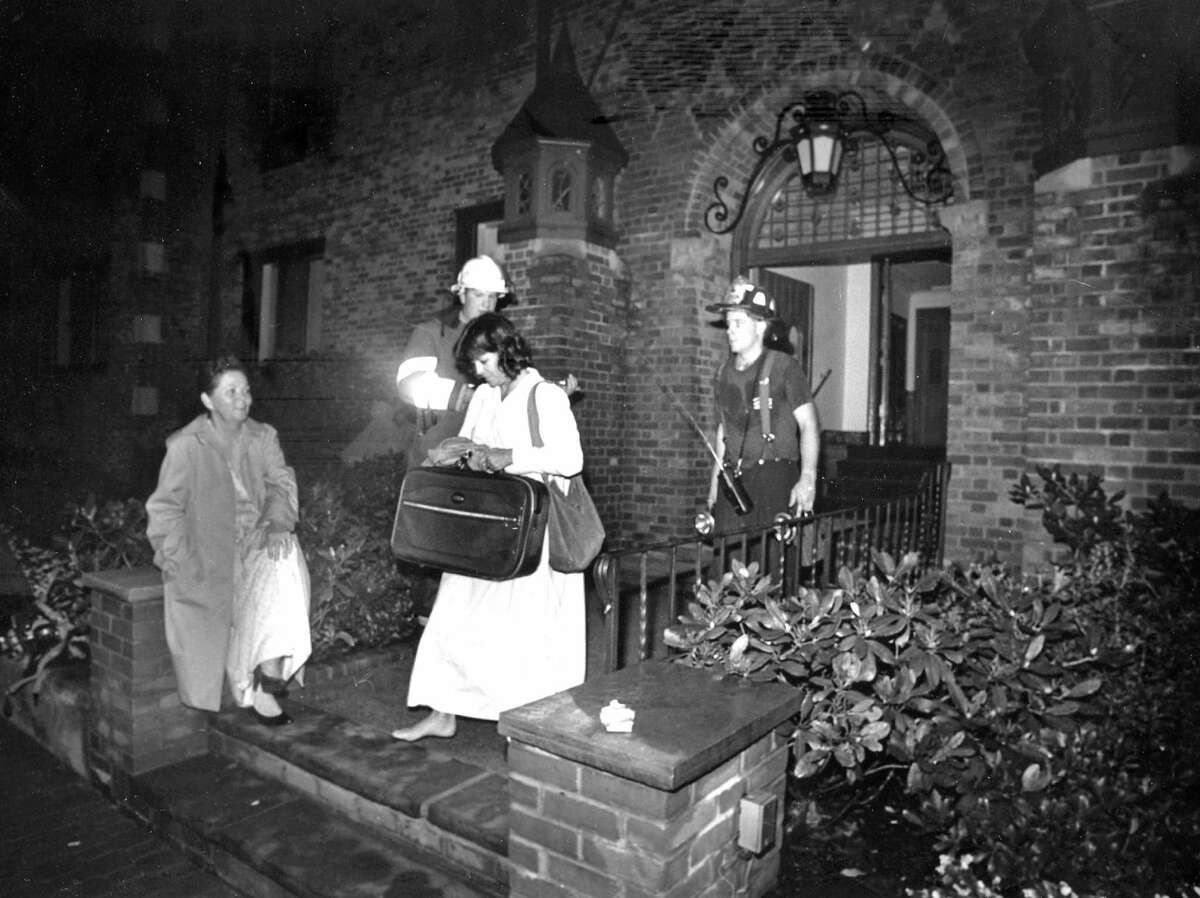 The resident manager of Greenwich Chateau, Bernice Hack, left, watches as the last person is evacuated from the Lafayette Court building, aided by firefighters, in the early morning of Sept. 21, 1988.