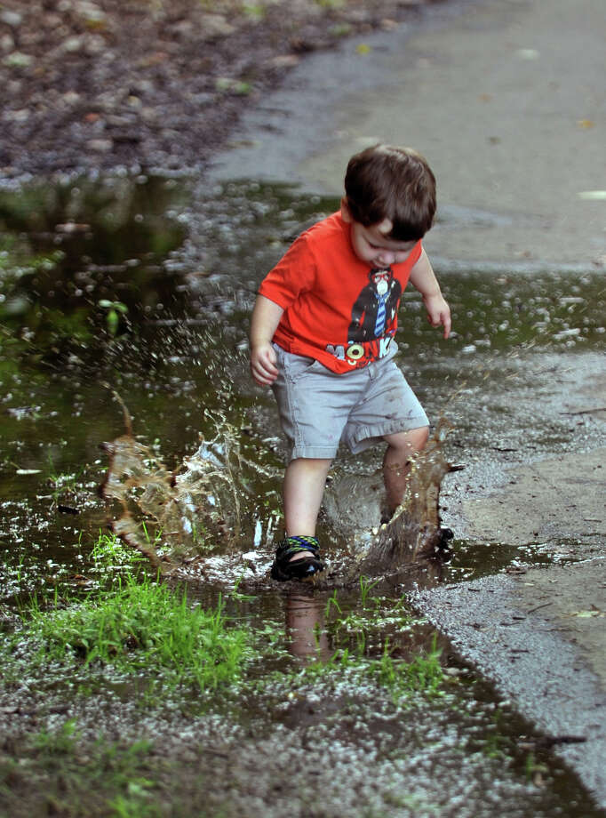 Levi Thompson, 2, of Trumbull, splashes around in a puddle while walking with his mom Jen at Twin Brooks Park in Trumbull, Conn. on Friday September 13, 2013. Photo: Christian Abraham / Connecticut Post