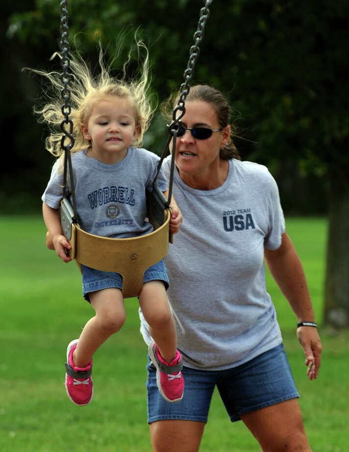 Babysitter Inga DeNunzio pushes Chloe Worrell, 3, on the swing set at Twin Brooks Park in Trumbull, Conn. on Friday September 13, 2013. Photo: Christian Abraham / Connecticut Post