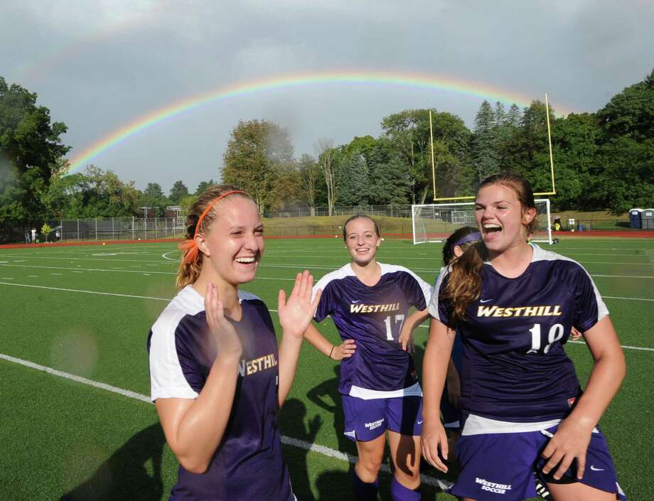 With a rainbow in the sky crowning their 1-0 victory over Greenwich, members of the Westhill High School girls varsity soccer team celebrate, from left, Rachel Benz, Claire Mioline and Jess Laszlo at Cardinal Stadium at Greenwich High School, Friday, Sept. 13, 2013. Laszlo scored what turned out to be the game winning goal late in the second half. Photo: Bob Luckey / Greenwich Time