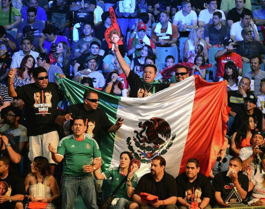 LAS VEGAS, NV - SEPTEMBER 13: Fans of boxer Canelo Alvarez cheer as they wait for the official weigh-in for the bout between Alvarez and Floyd Mayweather Jr. at the MGM Grand Garden Arena on September 13, 2013 in Las Vegas, Nevada. The fighters will meet in a WBC/WBA 154-pound title fight on September 14 in Las Vegas.