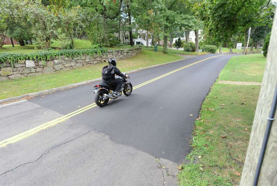 A motorcyclist drives down the recently paved Strickland Road in the Cos Cob section of Greenwich, Friday afternoon, Sept. 13, 2013. Photo: Bob Luckey / Greenwich Time