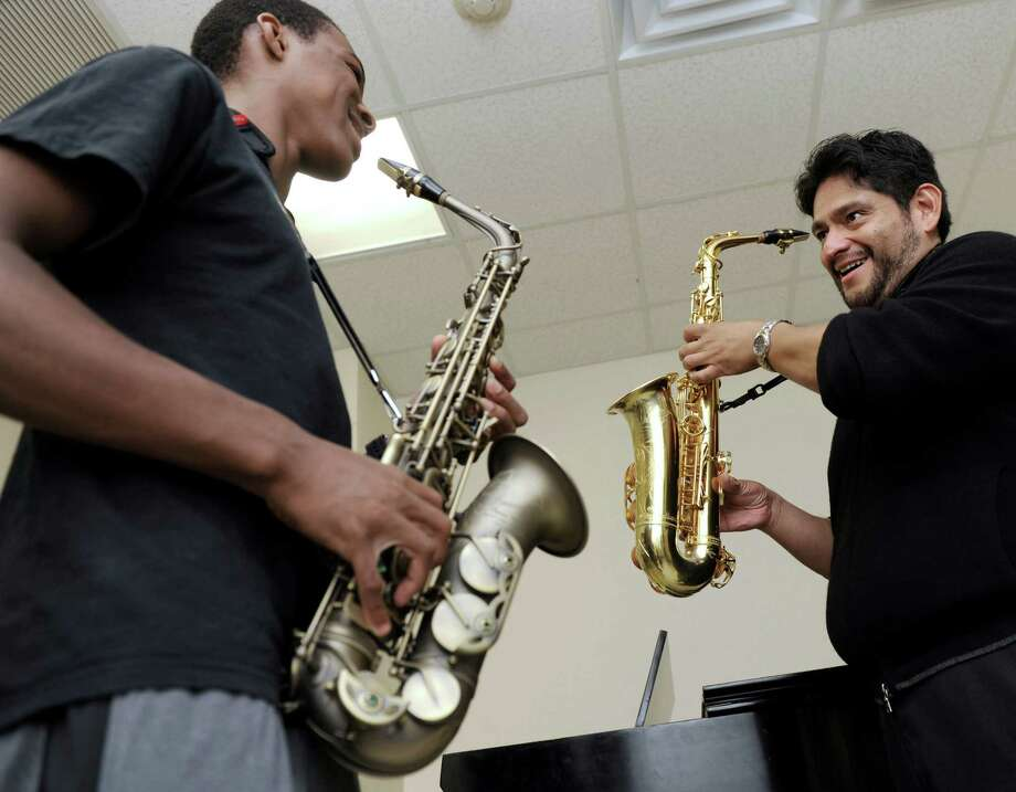 Saxaphonist Javier Oviedo, right, a part-time music teacher at Western Connecticut State University, in Danbury, Conn., teaches freshman Jeremiah Dorvil, 18, of Bridgeport, Friday, Sept. 13, 2013. Photo: Carol Kaliff / The News-Times