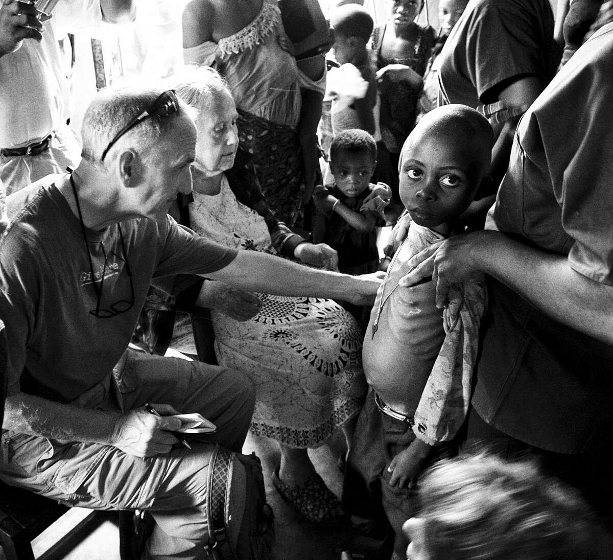 Jimmy Shafe (left), director of the Congo-Kasai chapter of Rivers of the World, and Cecile De Sweemer of Butoke examine a malnourished child in June in Congo.