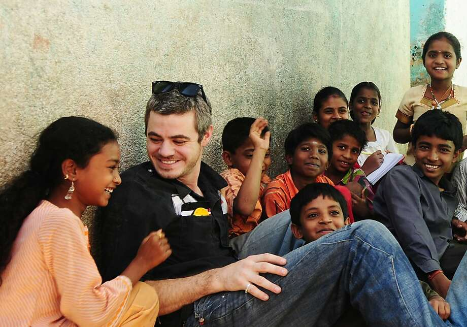 Scott Harrison sits with a group of children in Orissa, India, where his Charity: water is supporting a local project. Photo: Handout Photo, Charity:water