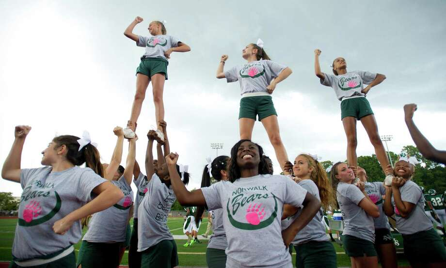 Norwalk cheerleaders support their team during Friday's football game against Westhill at Norwalk High School on September 13, 2013. Photo: Lindsay Perry / Stamford Advocate