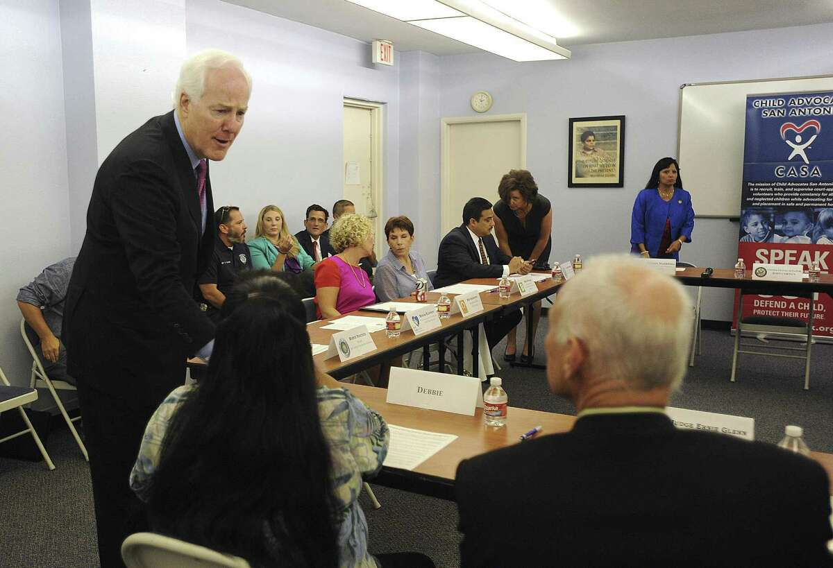 U.S. Sen. John Cornyn greats a survivor of human trafficking during a meeting in the offices of Child Advocates San Antonio. Cornyn is co-author of a bill targeting human trafficking.