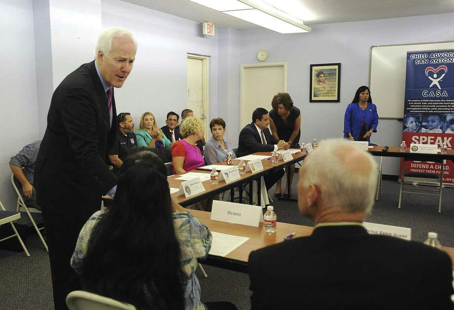 U.S. Sen. John Cornyn greats a survivor of human trafficking during a meeting in the offices of Child Advocates San Antonio. Cornyn is co-author of a bill targeting human trafficking. Photo: Billy Calzada / San Antonio Express-News
