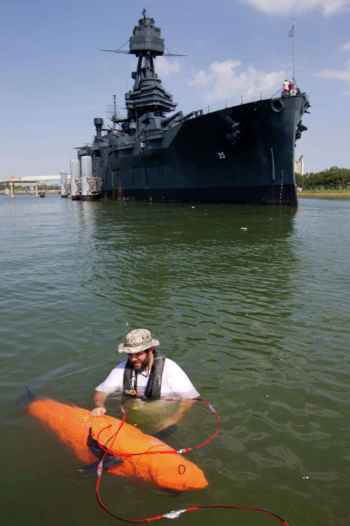 Mike Conry, with Boston Engineering's Advanced Systems Group, adjusts the robotic BIOSwimmer for a sweep of the Battleship Texas' hull for leaks.