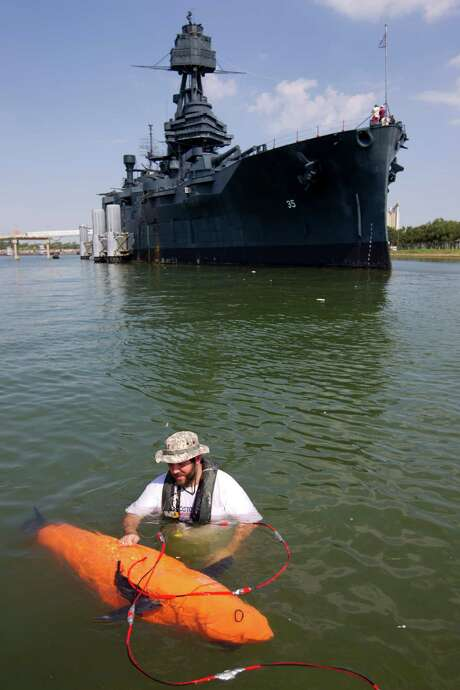 Mike Conry, with Boston Engineering's Advanced Systems Group, adjusts the robotic BIOSwimmer  for a sweep of the Battleship Texas' hull for leaks. Photo: Johnny Hanson, Staff / © 2013  Houston Chronicle