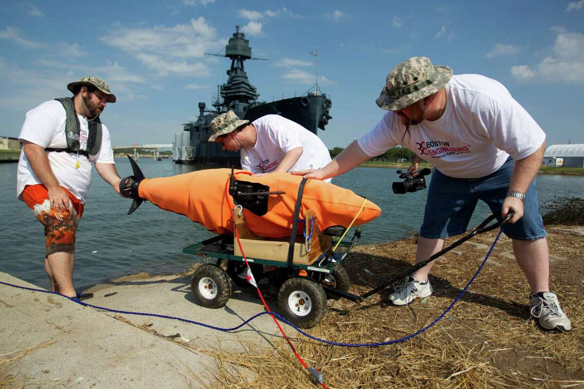 Andrew Keefe, center, is flanked by Mike Conry, left, and Mike Rufo as they prepare to place a tuna-inspired robotic submersible into the Houston Ship Channel, where it was being tested Friday under the hull of the Battleship Texas.