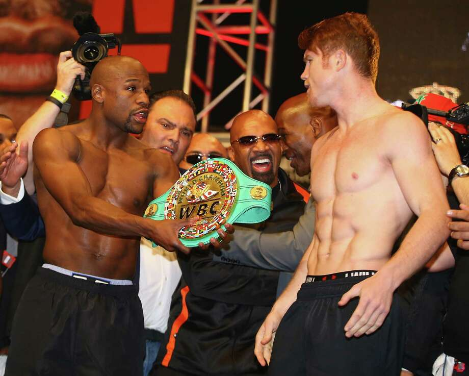 LAS VEGAS, NV - SEPTEMBER 13:  Boxers Floyd Mayweather Jr. (L) offers Canelo Alvarez his championship belt during the official weigh-in for their bout at the MGM Grand Garden Arena on September 13, 2013 in Las Vegas, Nevada. The fighters will meet in a WBC/WBA 154-pound title fight on September 14 in Las Vegas.  (Photo by Al Bello/Getty Images) ORG XMIT: 177598163 Photo: Al Bello / 2013 Getty Images
