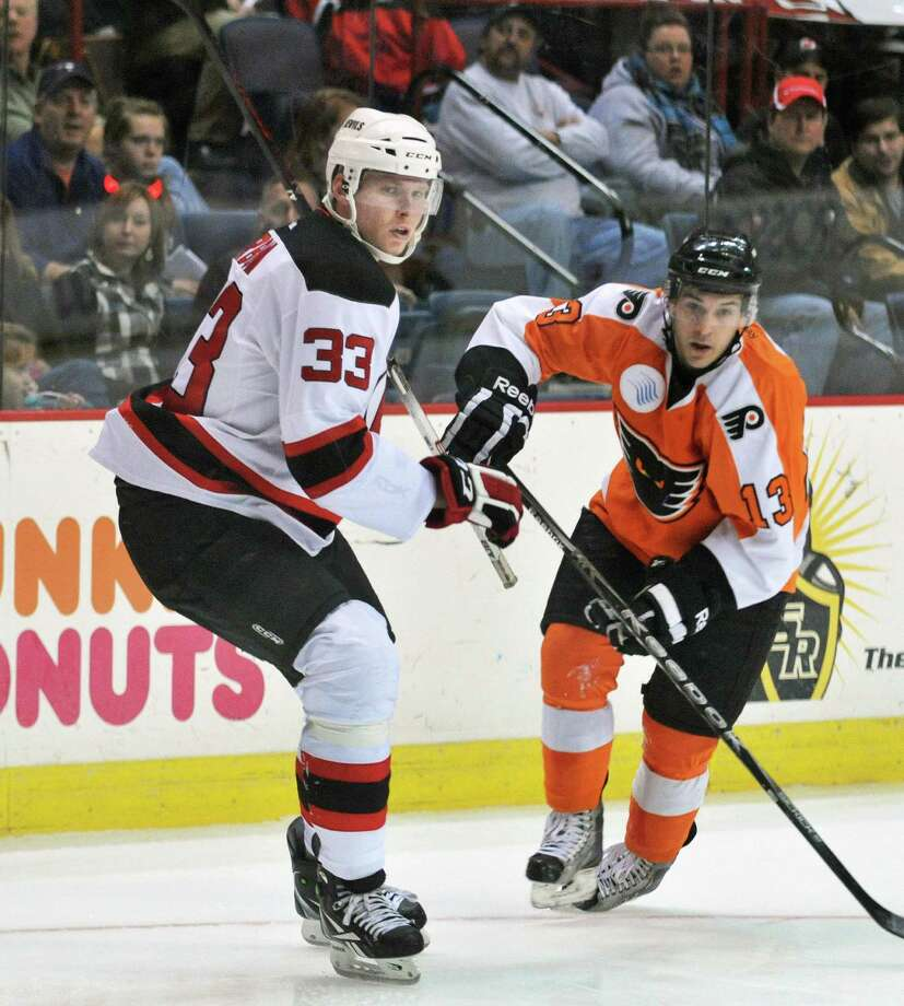 Devils #33, Alexander Urbom, left, and Adirondack Phantoms' #13 Garrett Roe during Saturday's game at the Times Union Center in Albany Jan. 28, 2012.   (John Carl D'Annibale / Times Union) Photo: John Carl D'Annibale / 10015984D
