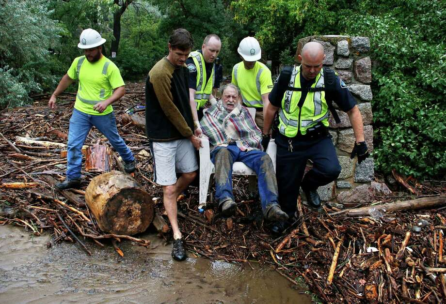 Will Pitner is rescued by emergency workers, and neighbor Jeff Writer, left, after a night trapped sheltering outside on high ground above his home as it filled with water from a surge of water, after days of record rain and flooding, at the base of Boulder Canyon, Colo., Friday Sept. 13, 2013 in Boulder. Flash flooding in Colorado has left at least three people reportedly dead and the widespread high waters have hampered emergency workers' access to affected communities as heavy rains hammered northern Colorado. (AP Photo/Brennan Linsley) ORG XMIT: COBL107 Photo: Brennan Linsley / AP