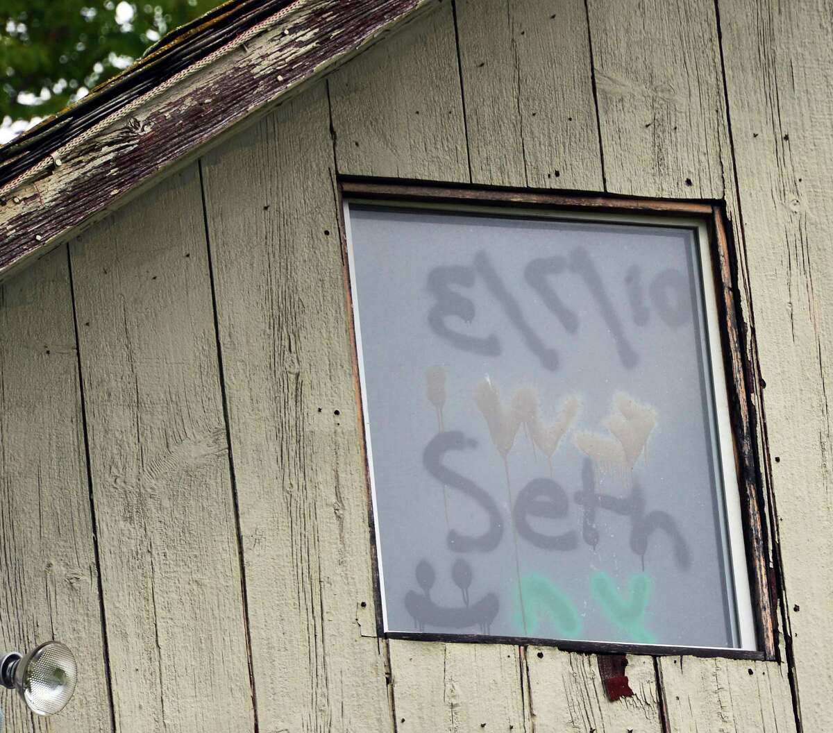 Graffiti in the window of a building at the seasonal home of former NFL star Brian Holloway Thursday, Sept. 12, 2013, in Stephentown, N.Y. (John Carl D'Annibale / Times Union)