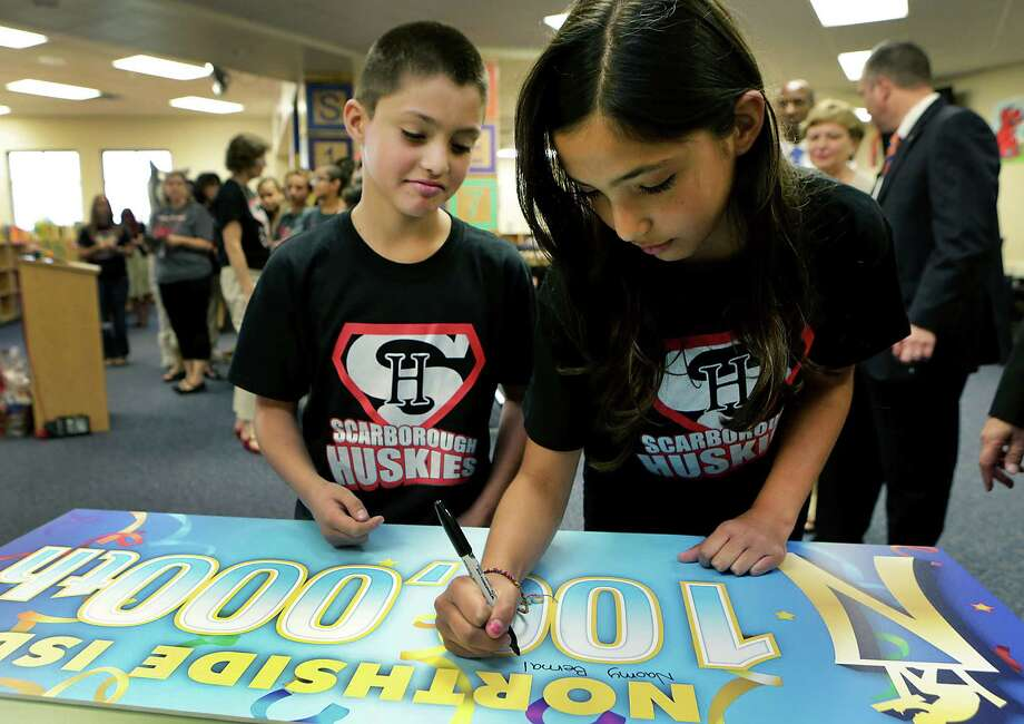 Naomy Bernal, 9, and brother Raul Bernal, 7, were surprised by the ceremony at Scarborough Elementary School. Photo: Bob Owen / San Antonio Express-News